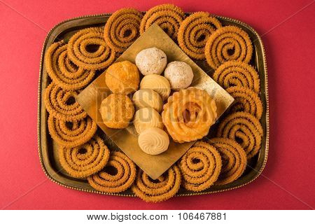 diwali snacks chakali or chakli, bundi laddu, jalebi, pedha or pera, coconut laddu in a brass tray o
