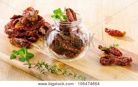 Italian Sun Dried Tomatoes In A Glass Jar On  Wooden Table.