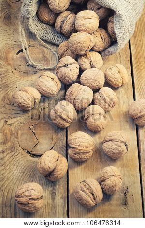 Pile Of Walnuts In Shell Inbag On A Wooden Background