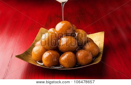 Gulab Jamun served in a square brass plate with pouring sweet syrup - An Indian sweet dish, round sh