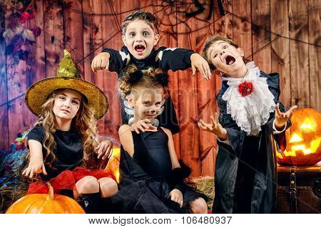 Cheerful children in halloween costumes celebrating halloween in a wooden barn with pumpkins. Halloween concept.