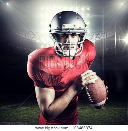 Portrait of determined sportsman holding American football against american football arena