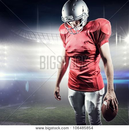 American football player looking down while standing against american football arena