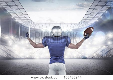 Full length rear view of American football player holding ball against rugby stadium