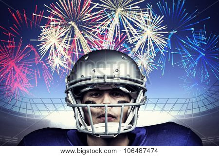 Portrait of determined American football player in uniform against fireworks exploding over football stadium