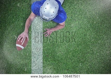 Rear view of American football player lying in front with ball against pitch with line