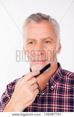 Confident Aged Man Combing His Beard