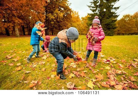 childhood, leisure, autumn, friendship and people concept - group of children collecting leaves in park