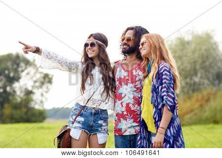 nature, summer, youth culture and people concept - smiling young hippie friends in sunglasses pointing finger to something on green field