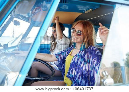 summer holidays, road trip, vacation, travel and people concept - smiling young hippie women driving and having fun in minivan car