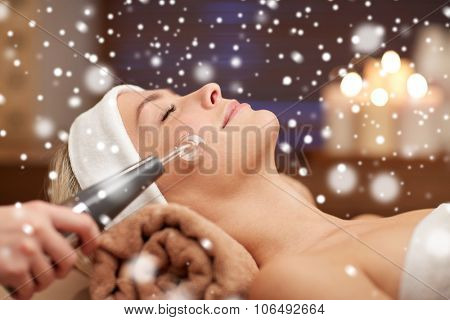 people, beauty, spa, cosmetology and technology concept - close up of beautiful young woman lying with closed eyes having face massage by massager and beautician in spa with snow effect
