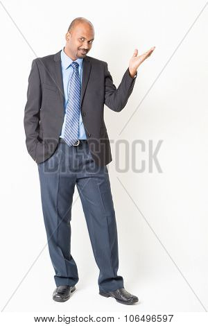 Portrait of full body mature Indian business man hand showing something, standing on plain background.