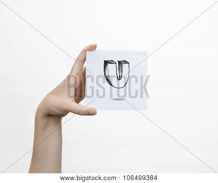 Hand Holding A Piece Of Paper With Sketchy Capital Letter  U, Isolated On White.
