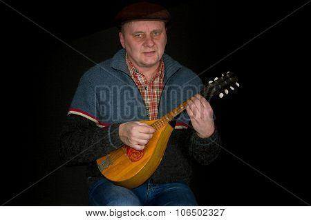 Portrait of mature man with mandolin against dark background