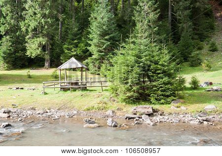 A Wooden Arbor Near A Mountain River