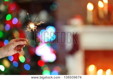 Female hand holding beautiful sparkler on Christmas background at home