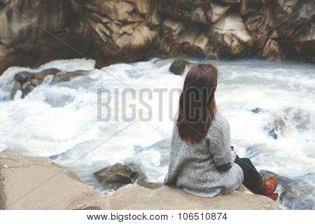 Photography of woman near beautiful waterfall on rocks