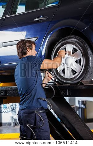 Rear view of male mechanic refilling car tire at auto repair shop