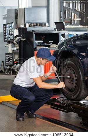 Male mechanic crouching while fixing car tire at repair shop