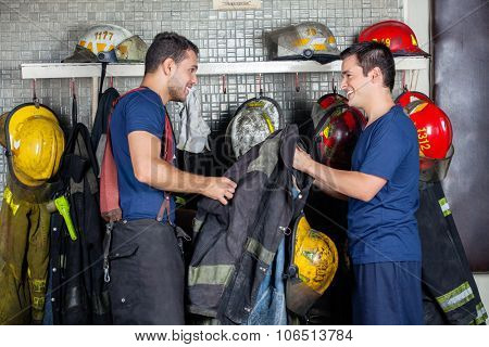 Happy firefighters looking at each other while holding jacket in fire station