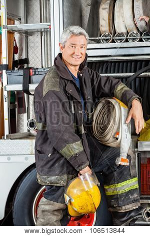 Portrait of confident male firefighter standing by truck at fire station