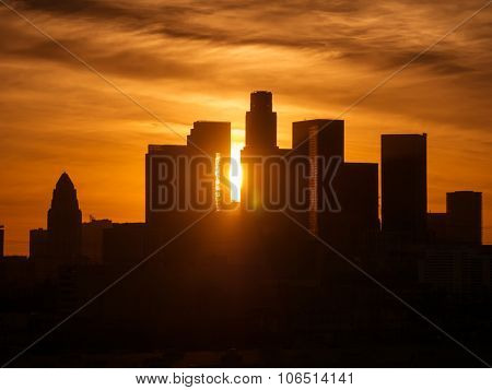Sun peeking between buildings of downtown Los Angeles skyline at sunset.