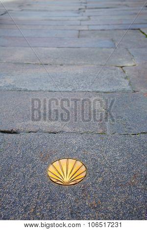Santiago de Compostela end of Saint James Way golden shell sign on soil in Galicia Spain