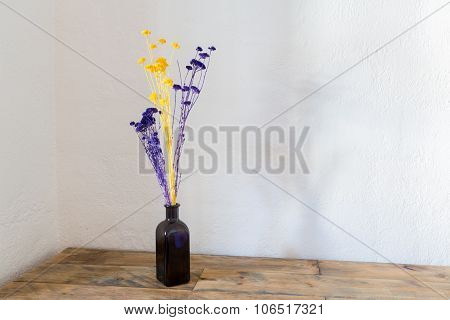 Dried Flowers In Blue Bottle Vase On Wood