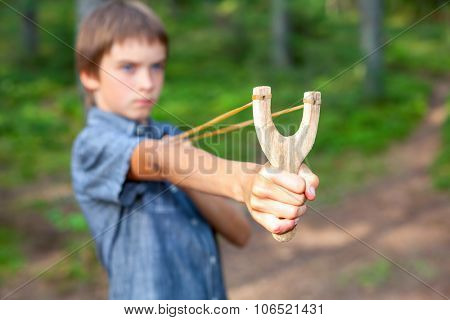 Boy aiming wooden slingshot outdoors, , focus on a slingshot face is blurred