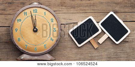 vintage clock and empty chalkboard over grunge background