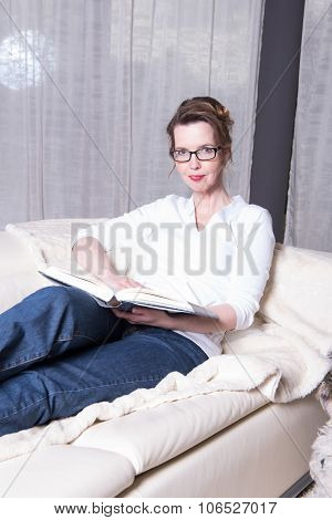 Attractive Woman On Couch Reading A Book