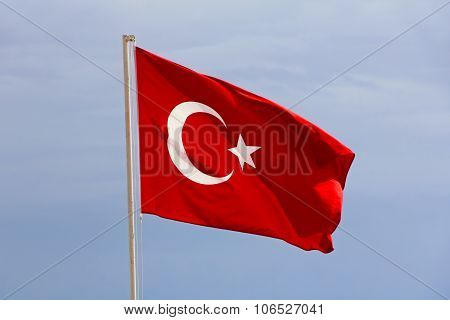Turkish Flag Against Of The Blue Sky.