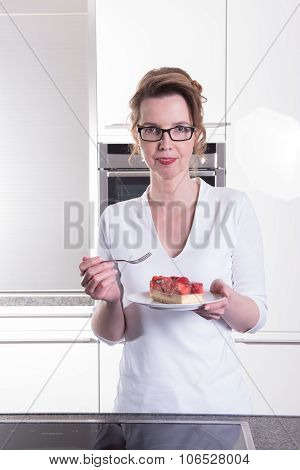 Attractive Woman In Modern Ktchen Eating Strawberry Cake