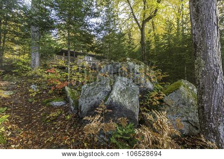 Cottage In Autumn With Large Rocks In The Foreground