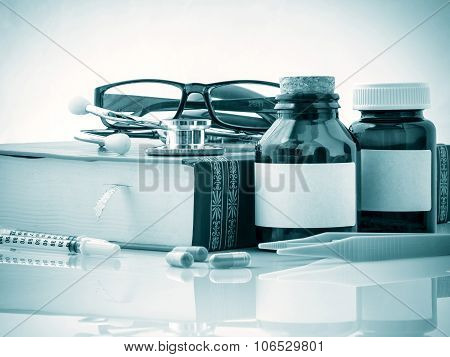 Stethoscope On A Textbooks And Bottle Of Pills Blue Tone .