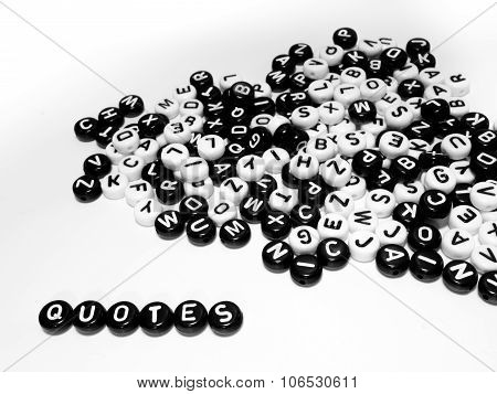Heap of round letters black and white and quotes word written by side