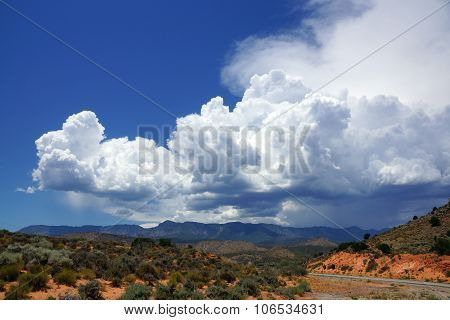 A Winding Road Through A Desert In Utah And Blue Cloudy Sky