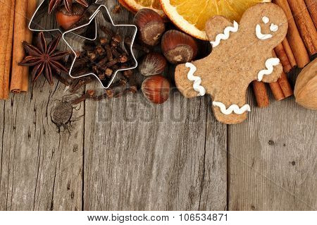 Christmas baking ingredients and gingerbread man border on rustic wood