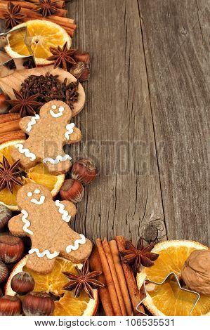 Christmas baking ingredients with gingerbread men corner border on wood