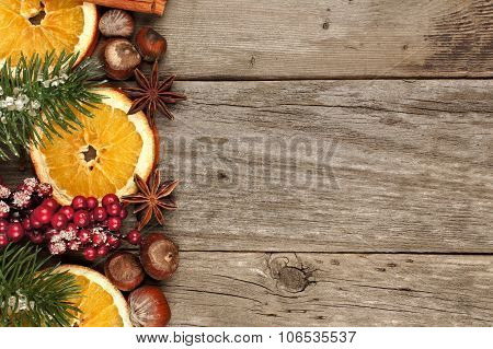 Christmas border with branches, nuts and orange slices on wood