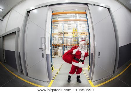 Santa Claus with red sack leaving the gate to storehouse full of presents