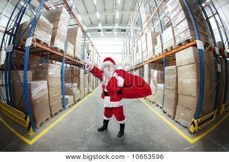 Santa Claus with sack of gifts, ringing in a bell in storehouse full of gifts