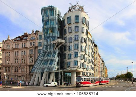 Dancing House in Prague with red tram in front