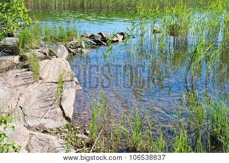 Lake edge with red granite rocks
