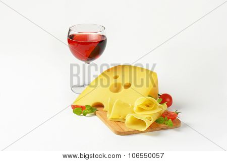 fresh cheese on wooden cutting board and glass of red wine