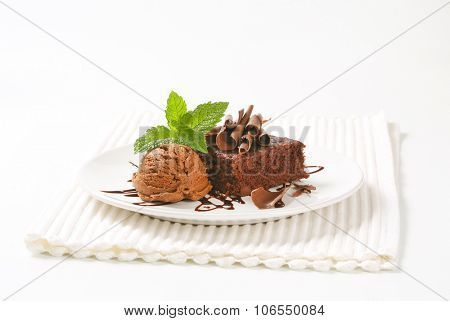 brownie cake and scoop of chocolate ice cream on white plate and place mat