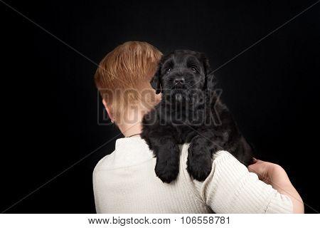 puppy big black terrier and women in black background