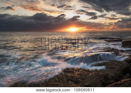 Seascape with sun trail over rocks and water