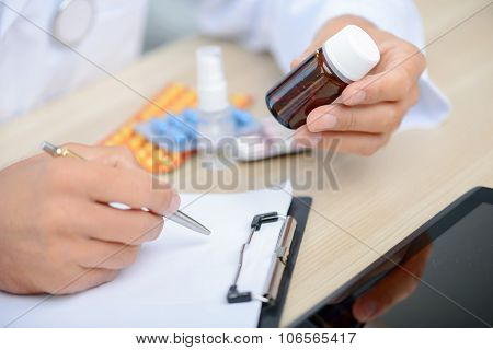 Positive doctor holding pills