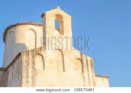 Ancient Medieval Stone Church Lit By Warm Sunset Light Against Blue Clear Sky Background